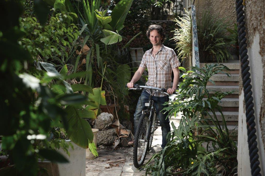 Itay Remer, an Azrieli Graduate Studies Fellow, rides a bike through foliage.