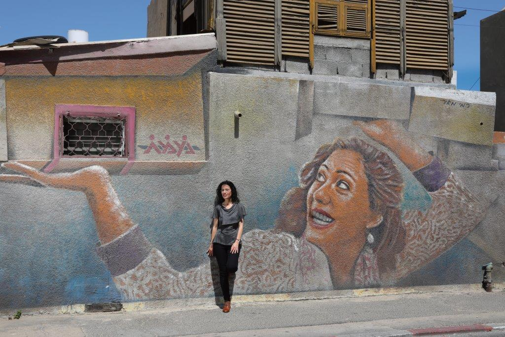 Meytal Nasie, an Azrieli Graduate Studies Fellow, leans against a mural.