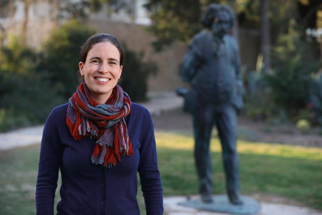 Mor Nitzan, an Azrieli Graduate Studies Fellow, poses with a statue of Albert Einstein.