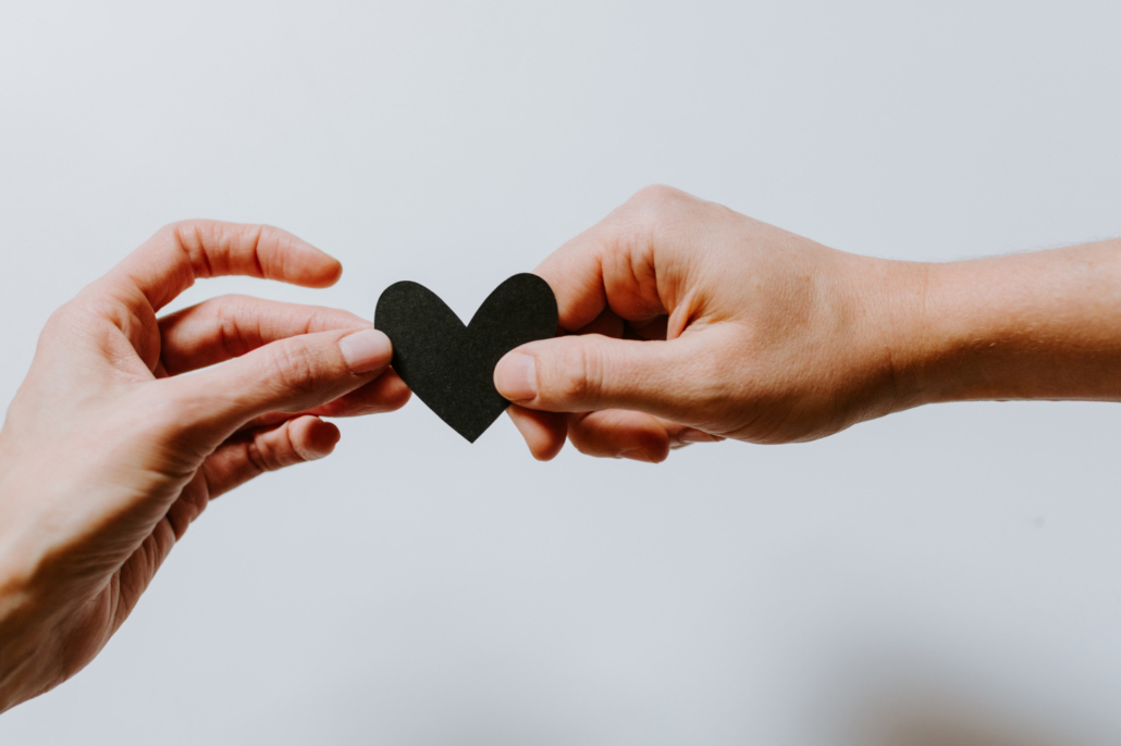 Two hands holding paper cut-out of a heart